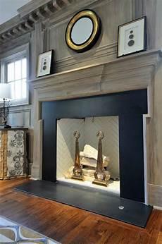Back To Back Fireplace Design Gray Washed Millwork Black Stone Fireplace Surround