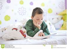 boy in his bed reading a book stock image image of