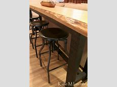 live edge bar table with metal industrial stools in man friendly room with laminate flooring