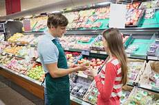 Retail Store Assistant Shop Assistant Giving Advises To A Customer In A Grocery