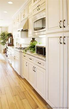 White Kitchen Cabinets Light Floor Antique White Kitchen With Wood Floors And An Island Sink