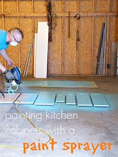 painting the kitchen cabinets with a paint sprayer dans