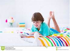 school boy reading a book in bed stock image image of