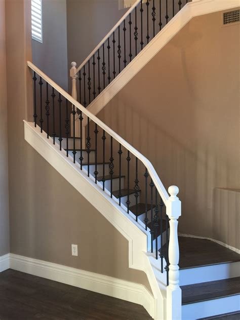 white railing with black spindles wood stairs with white