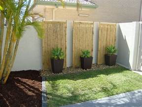 tall planters and rocks against wall lined by stones small yard landscape ideas pinterest