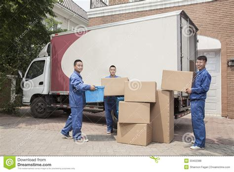 Moving On And Moving In by Movers Unloading A Moving Many Stacked Cardboard