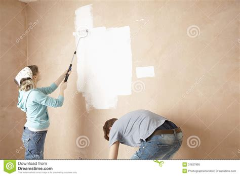 looking for a man who paints houses woman painting and man bending in unrenovated house stock