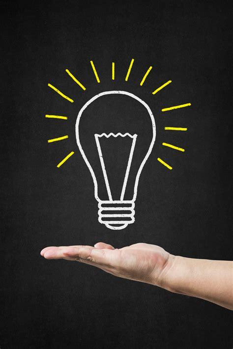hand holding  bulb drawn   blackboard photo