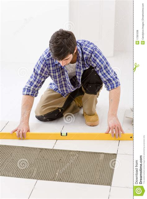 home tile improvement handyman with level stock photo