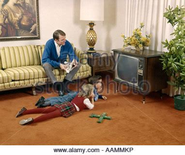 horse sitting on couch 1960s brother sister sitting on living room floor