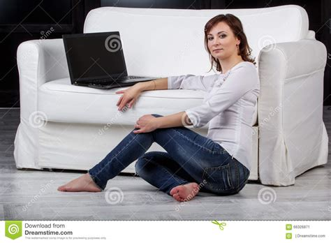 sitting in sofa girl sitting on the floor near the sofa stock photo