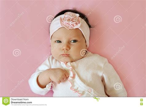 closeup of beautiful baby with flower headband stock photo portrait of a 2 month baby wearing lace flower