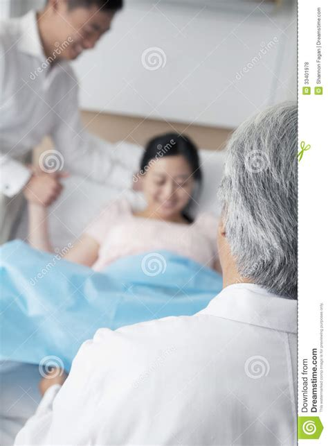 in labor in labor holding husbands with doctor in the foreground in the hospital