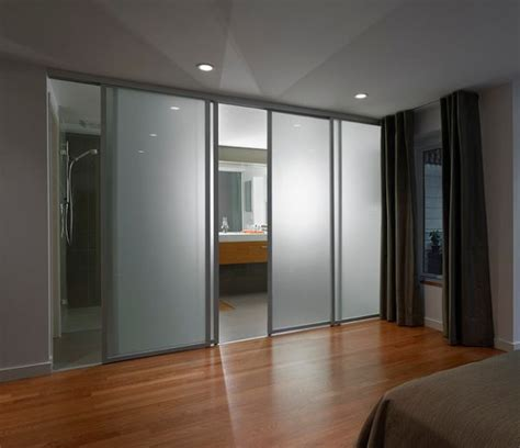 Frosted glass sliding doors separate the contemporary bedroom from the