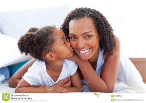 two girls kissing in bed loving little girl kissing her mother lying on bed stock