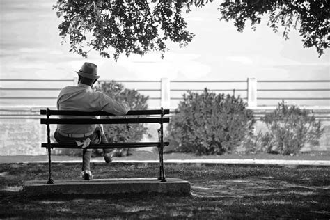 old people on a bench man sitting on a bench in battery park charleston in
