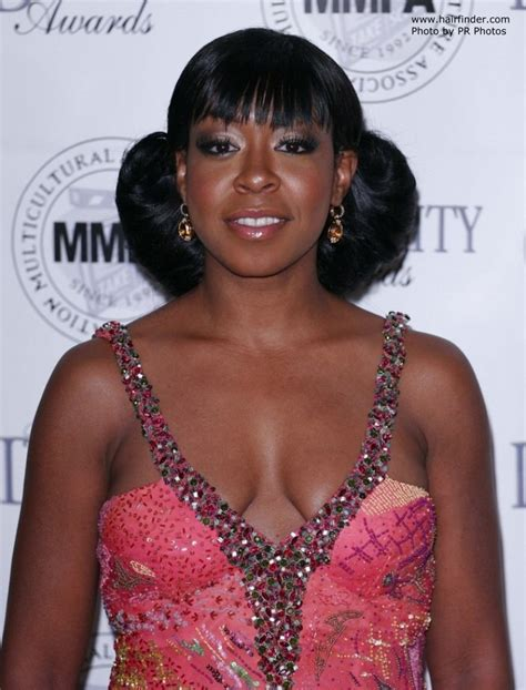 Tichina Arnold with her hair put up in such a way that it