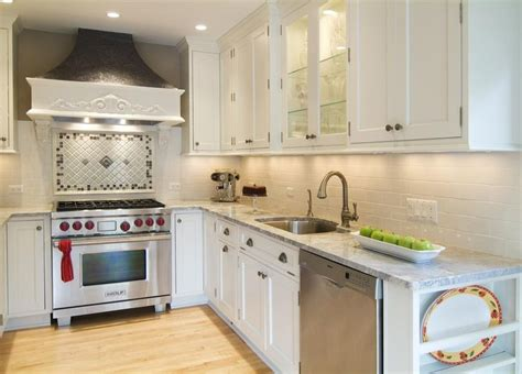 small kitchen with white cabinets stove backsplash mosaic kitchen stove table and chairs and islands