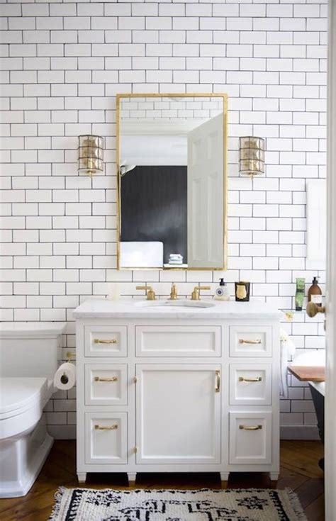 white tile dark grout bathroom white cabinets with brass hardware vintage bathroom