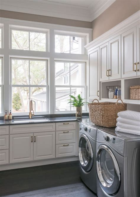 bright laundry room white cabinets brass fixtures and