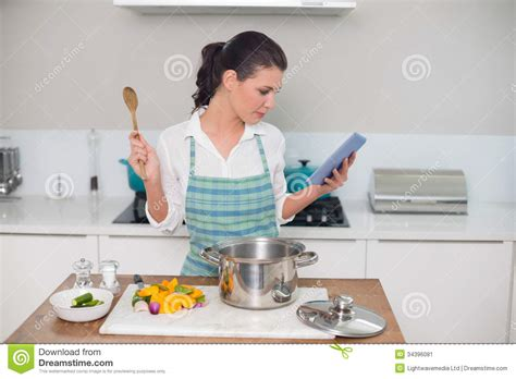 What Do You Wear While Cooking by Focused Gorgeous Wearing Apron Using Tablet While