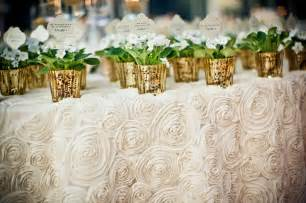 Wedding Table Cloths Ivory Rosette Wedding Tablecloth With Potted Gold Favors Onewed Com