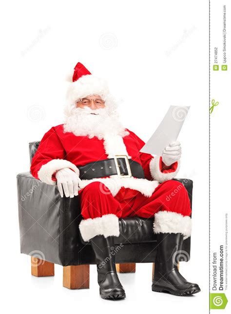 santa claus sitting in armchair and reading letter stock