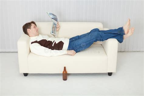 lying on a sofa person comfortably lie on sofa with journal stock photo