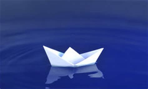 origami boat real paper boat floating over blue real water royalty free