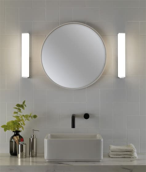 vertical fixtures or sconces mounted on either side of the rectangular chrome and polycarbonate opal diffuser wall