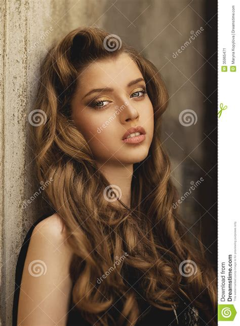 girl with brown hair and gold eyes young beautiful girl with long hair and gold make up in