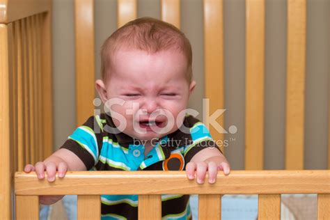 Crying Unhappy Baby Standing In Crib Stock Photos Baby Cries In Crib