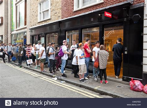 supreme uk youths queue outside supreme shop soho