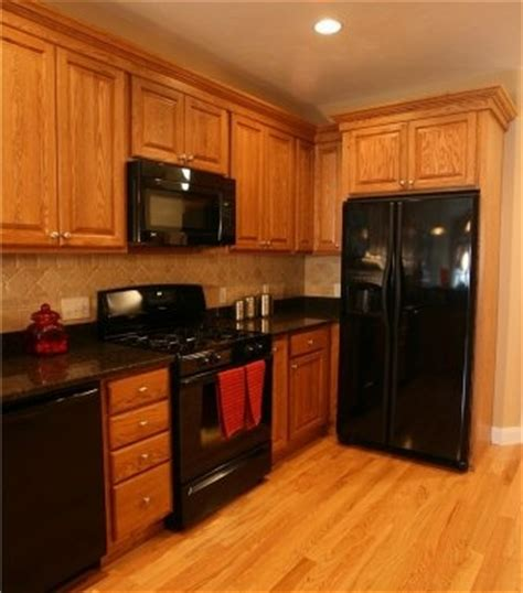 kitchen with oak cabinets with black appliances thinking