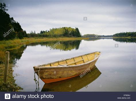 small boat on water a small wooden dory or rowing boat moored on flat calm