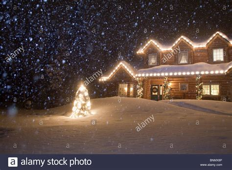 log home decorated with christmas lights with snow falling