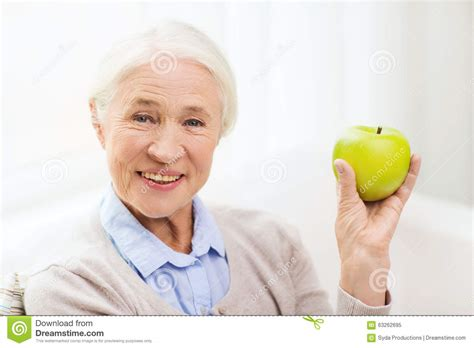 happy senior with green apple at home stock photo