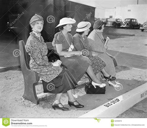 sitting on the bench waiting for you four women sitting on a bench waiting for the bus stock