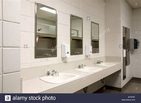 public bathroom mirror perspective shot of a counter top with three sinks and