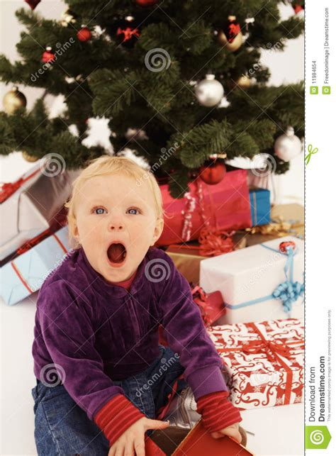 christmas surprised child opening gifts stock photo