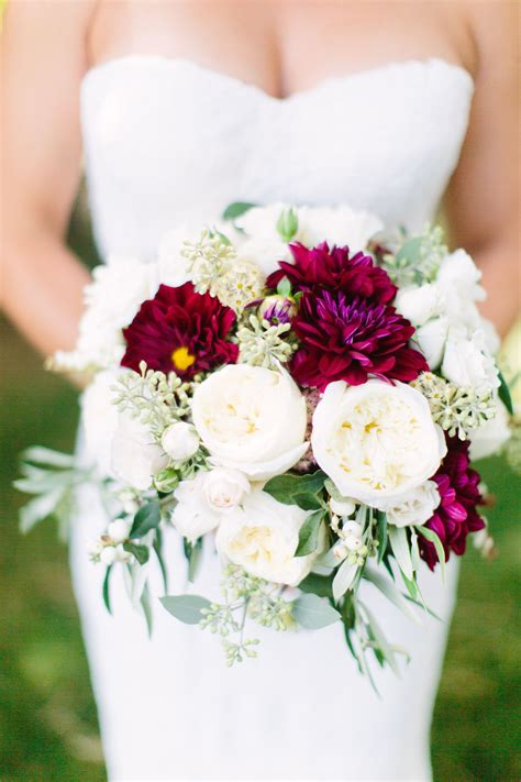roses dahlias and peonies in shades of ivory and burgundy this with pine and turqoise mixed