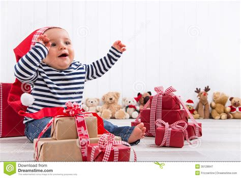 first christmas baby unwrapping a present royalty free