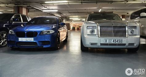 roll royce bmw bmw m5 poses next to rolls royce phantom coupe in dubai