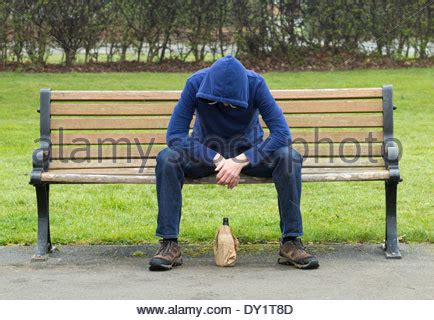 bench drinking male wearing hoodie sitting on park bench drinking alcohol