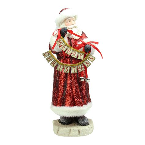 red glittered santa claus holding merry christmas sign  bells christmas figurine