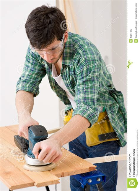 home improvement handyman sanding wooden floor royalty