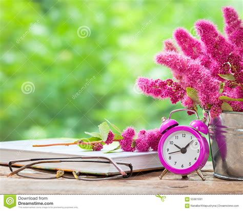 Bunch Of Flowers In A Vase Flowers In Bucket Pink Alarm Clock And Book Stock Photo