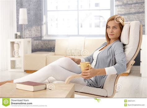 woman in armchair attractive woman in armchair with coffee mug stock image
