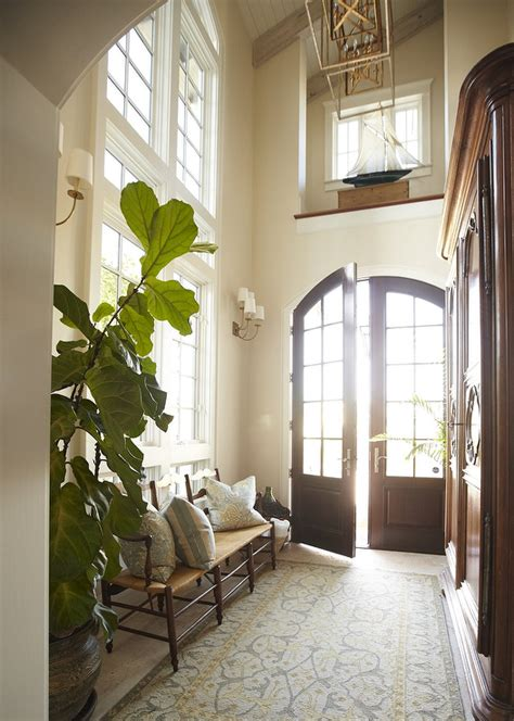 2 Story Foyer Decorating Ideas by Two Story Foyer With Stacked Mirrors Bench