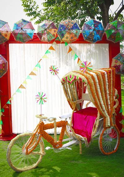 Colourful mehendi photobooth with decorated rikshaw